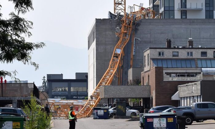 A worker looks on as a police officer investigates a collapsed crane resting on the building it damaged in Kelowna, B.C., Canada, on July 12, 2021. (The Canadian Press/Alistair Waters)