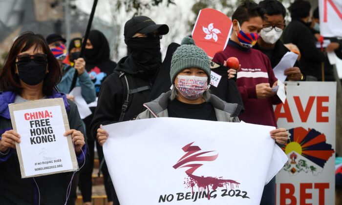 Activists including members of the local Hong Kong, Tibetan and Uyghur communities hold up banners and placards in Melbourne, Australia, on June 23, 2021, calling on the Australian government to boycott the 2022 Beijing Winter Olympics over China's human rights record. (William West/AFP via Getty Images)