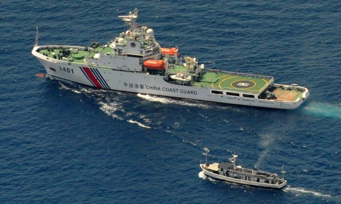 A China Coast Guard ship (top) and a Philippine supply boat engage in a standoff as the Philippine boat attempts to reach the Second Thomas Shoal, a remote South China Sea reef claimed by both countries, on March 29, 2014. (Jay Directo/AFP via Getty Images)