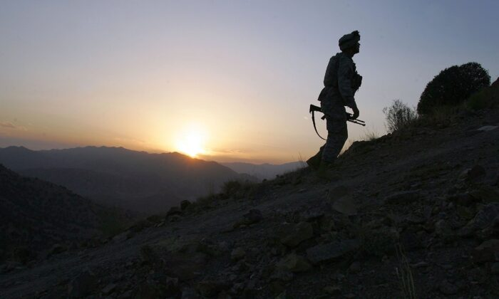A U.S. Army soldier climbs a hill towards an American outpost near Camp Tillman, Afghanistan, just two kilometers from the Pakistan border, on Oct. 15, 2006. (John Moore/Getty Images)