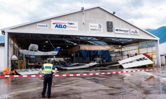 A hangar and some of the parked small planes at the local airport of Locarno in Magadino, southern Switzerland were heavily damaged after a thunderstorm on July 13, 2021. (Ti-Press/Elia Bianchi/Keystone via AP)