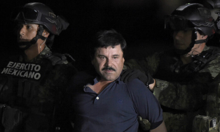 """Drug kingpin Joaquin """"El Chapo"""" Guzman is escorted into a helicopter at Mexico City's airport following his recapture by the Mexican military in Los Mochis, in Sinaloa State on Jan. 8, 2016. (Alfredo Estrella/AFP/Getty Images)"""