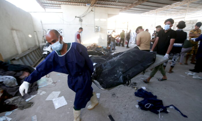 Men carry stretchers with body bags containing the remains of victims after a fire broke out at al-Hussain coronavirus hospital in Nassiriya, Iraq, on July 13, 2021. (Essam al-Sudani/Reuters)