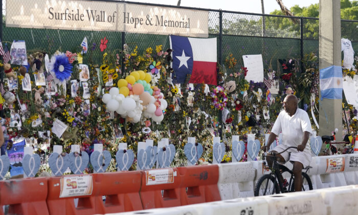 A cyclist rides past a makeshift memorial recognizing the victims of the partially collapsed Champlain Towers South building, as removal and recovery work continues at the site, in Surfside, Fla., on July 13, 2021. (Lynne Sladky/AP Photo)