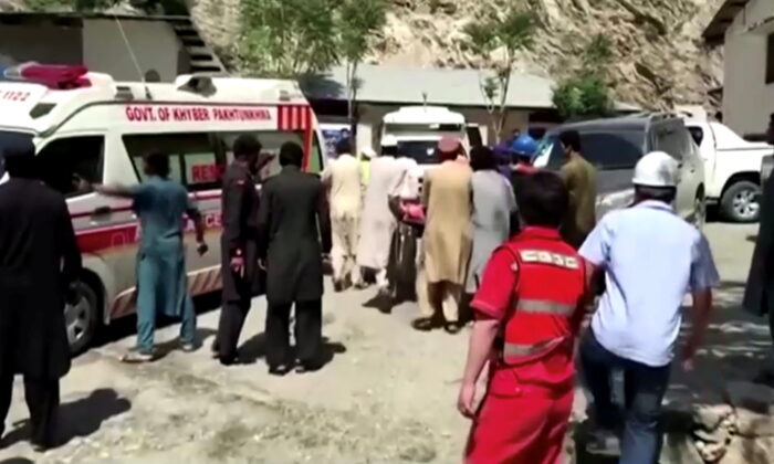 People wheel a gurney toward an ambulance outside a hospital in Dasu, Pakistan, after a bus with Chinese nationals on board plunged into a ravine in Upper Kohistan following a blast on July 14, 2021, in this still image taken from video. (Reuters/Reuters Tv)