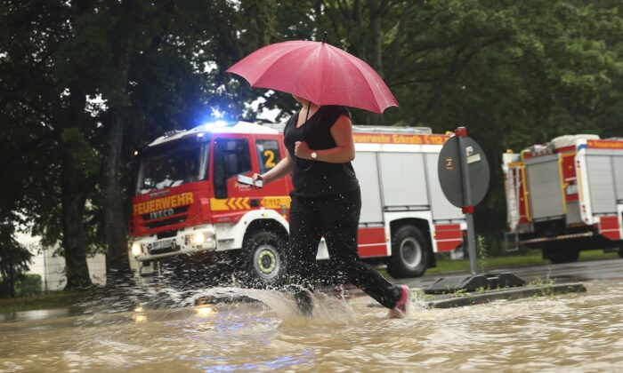 A woman walks past fire trucks at a flooded street with an umbrella Duesseldorf, Germany, on July 14, 2021. (David Young/dpa via AP)