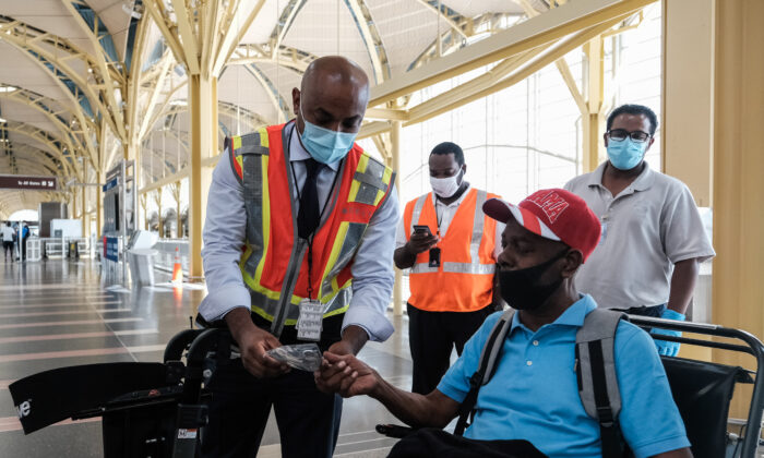 A Delta Airline employee gives a face mask to a passenger during check-in at the Ronald Reagan National Airport in Arlington, Va., on July 22, 2020. (Michael A. McCoy/Getty Images)