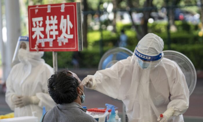 A man (L) is given a nucleic acid test for the Covid-19 coronavirus in Mangshi in the Dehong Dai and Jingpo Autonomous Prefecture, which borders Myanmar in China's southwestern Yunnan Province, on July 9, 2021. (STR/AFP via Getty Images)