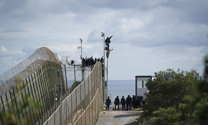African migrants attempt to scale the fence at the border between Morocco and the North African Spanish enclave of Melilla, on April 3, 2014. (Alexander Koerner/Getty Images)