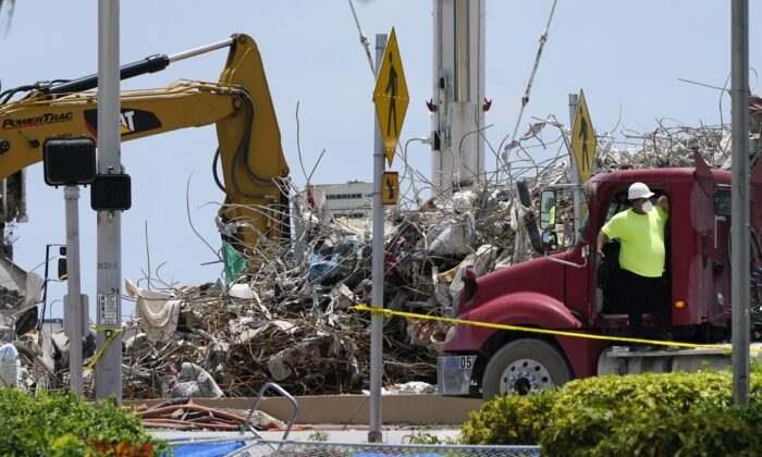A worker waits to load his truck with debris from the rubble of the Champlain Towers South building, as removal and recovery work continues at the site of the partially collapsed condo building in Surfside, Fla., on July 14, 2021. (Lynne Sladky/AP Photo)