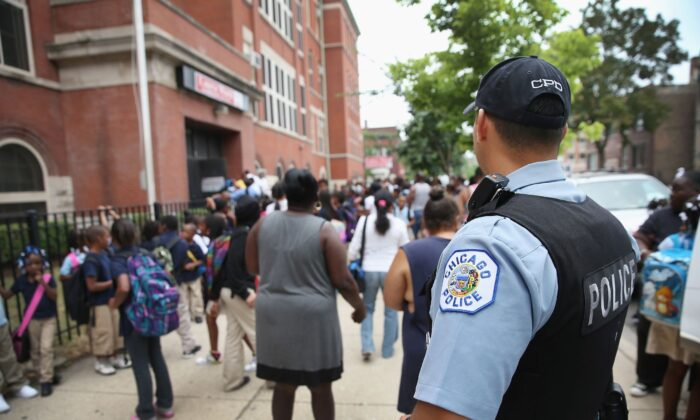 Chicago Probationary Police officer Juan Soto watches as students leave Laura Ward Elementary School on Chicago's West Side, on Aug. 28, 2013. (Photo by Scott Olson/Getty Images)