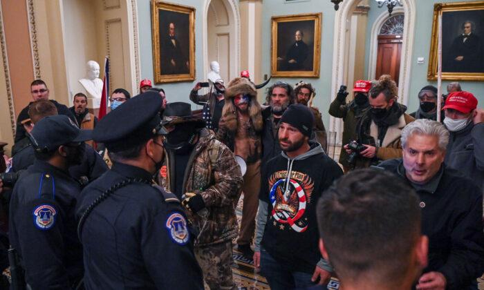 Douglas Jensen (C) speaks to U.S. Capitol Police officers inside the building in Washington on Jan. 6, 2021. (Saul Loeb/AFP via Getty Images)