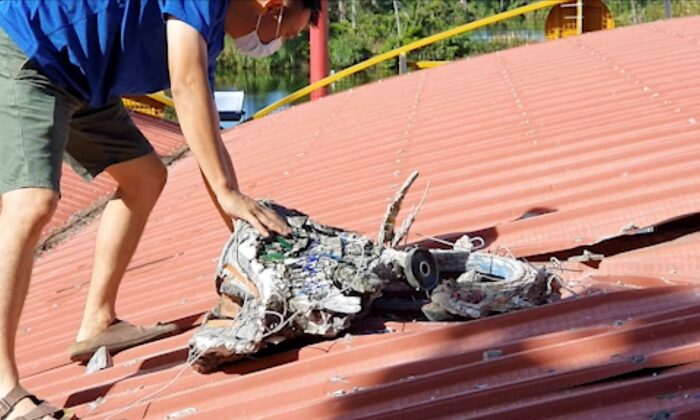 In this image taken from a video footage run by Taiwan's TTV via AP Video, a man checks the roof of a temple where a decorative piece fell and damaged the roof after multiple earthquakes struck the city of Hualien along the eastern coast of Taiwan, on July 14, 2021. (TTV via AP)