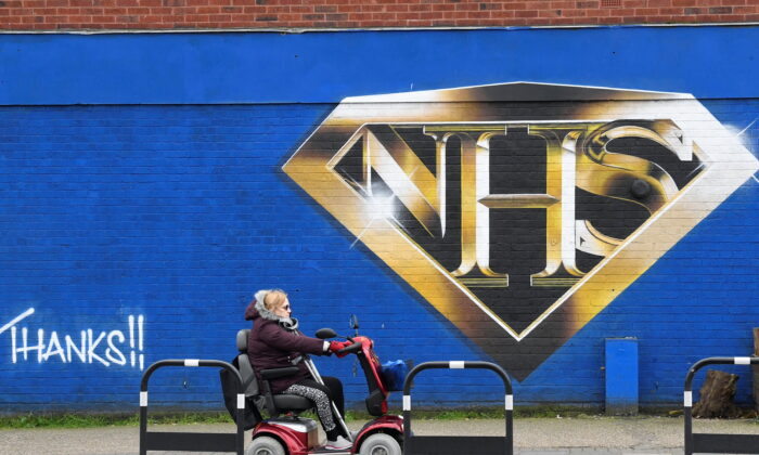 A woman on a mobility scooter drives past a mural praising the NHS, in London on March 5, 2021. (Toby Melville/Reuters)