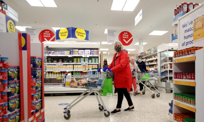 A woman wearing a mask pushes a shopping cart at a Tesco supermarket in Hatfield, United Kingdom, on Oct. 6, 2020. (Peter Cziborra/Reuters)