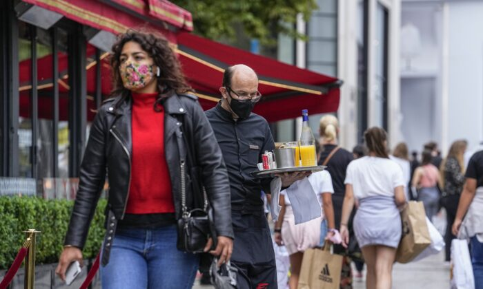 A waiter wearing a face mask to protect against coronavirus serves customers at the Champs Elysees avenue in Paris, on July 12, 2021. (Michel Euler/AP Photo)