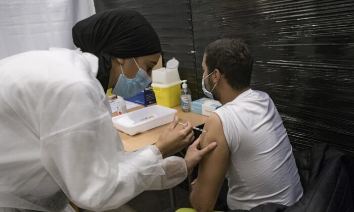 A nurse administrates the Pfizer COVID-19 vaccine to Thibaut Razafinarivo, 26, in a vaccination center in Versailles, west of Paris, on July 13, 2021. (Constantin Gouvy /AP Photo)
