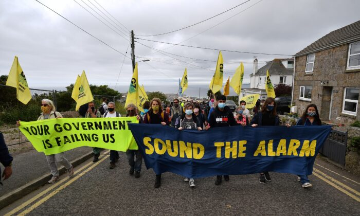 Activists from the climate change protest group Extinction Rebellion take part in a protest march  on the first day of the three-day G7 summit in St Ives, Cornwall, England, on June 11, 2021. (Ben Stansall/AFP via Getty Images)