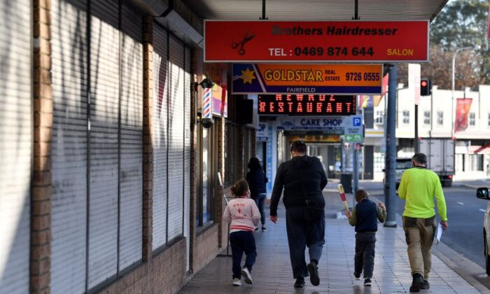 A family walk in front of shuttered shops during a lockdown in the Fairfield in Sydney, Australia, on July 12, 2021. (Saeed Khan/AFP via Getty Images)