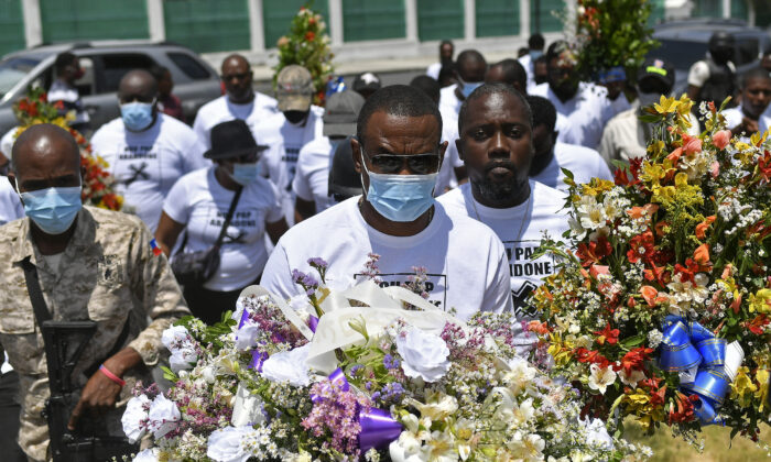 Men carry flowers to a spot outside the presidential palace in memory of slain President Jovenel Moise in Port-au-Prince, Haiti, on July 14, 2021. (Matias Delacroix/(AP Photo)