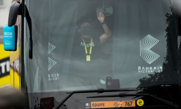 A member of the Bahrain Victorious team closes the curtains in team the bus prior to the eighteenth stage of the Tour de France cycling race over 129.7 kilometers (80.6 miles) with start in Pau and finish in Luz Ardiden, France, on July 15, 2021. (Christophe Ena/AP Photo)