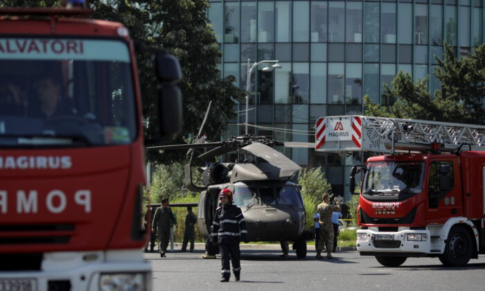 Romanian firefighters are seen near a military Black Hawk helicopter that made an emergency landing in central Bucharest, Romania, on July 15, 2021. (Inquam Photos/Octav Ganea via Reuters)