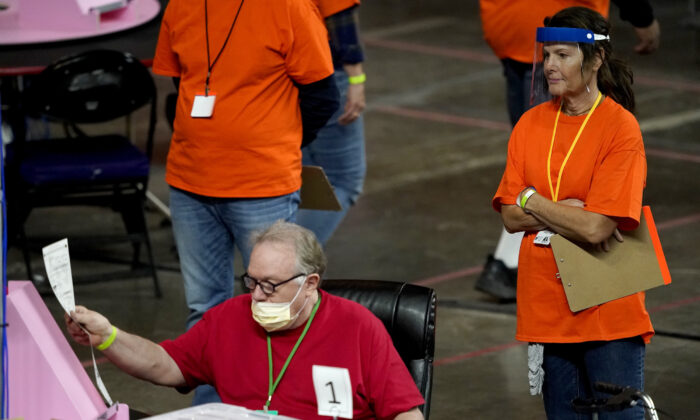 Maricopa County ballots cast in the 2020 general election are examined and recounted by contractors working for Florida-based company, Cyber Ninjas at Veterans Memorial Coliseum in Phoenix, Ariz., on May 6, 2021. (Matt York, Pool/AP Photo)