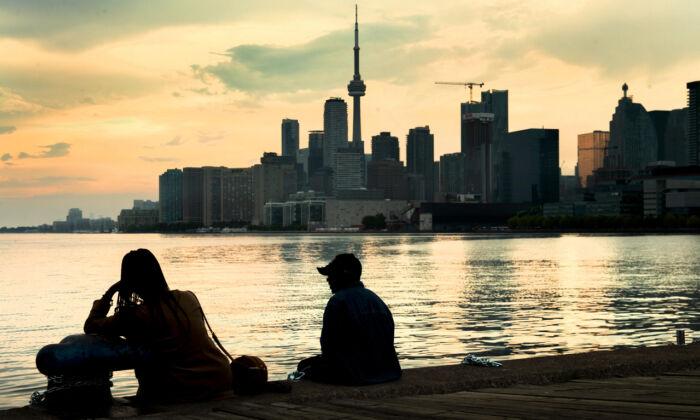 People watch the Toronto skyline on June 8, 2021. (The Canadian Press/Frank Gunn)