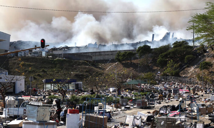 A factory burns in the background while empty boxes litter the foreground from looted goods being removed, on the outskirts of Durban, South Africa, on July 14, 2021. (AP Photo)