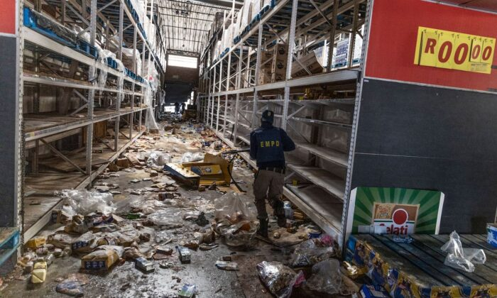 A member of the South African Police Services  searches for looters inside the Gold Spot Shopping Centre in Vosloorus, southeast of Johannesburg, on July 12, 2021. (Guillem Sartorio/AFP via Getty Images)