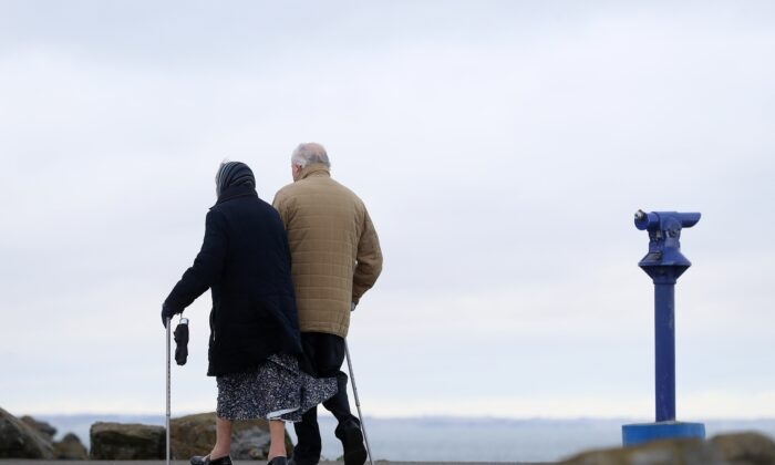 An elderly couple walking at unknown venue on Dec. 21, 2020. (Brian Lawless/PA)