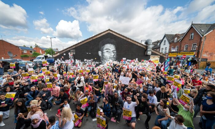 People taking the knee in front of a mural of Manchester United striker and England player Marcus Rashford on Copson Street, Withington, UK, on July 13, 2021. (Danny Lawson/PA)