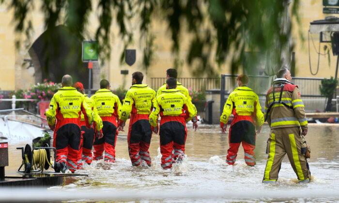 Lifeguards walk through a flooded street, following heavy rainfalls, in Valkenburg, Netherlands, July 15, 2021. (Piroschka Van De Wouw/Reuters)