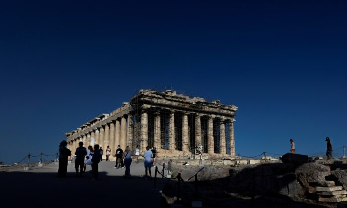 People visit the Parthenon temple atop the Acropolis hill in Athens, Greece, on June 8, 2021. (Alkis Konstantinidis/Reuters)
