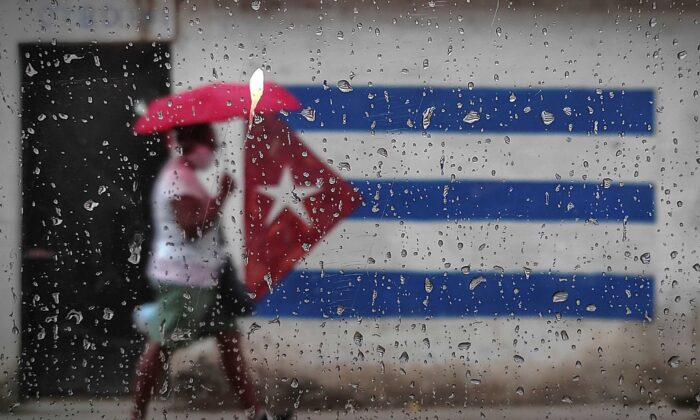A woman walks near a graffiti with the Cuban flag in Havana on Jan. 12, 2021. (Yamil Lage/AFP via Getty Images)