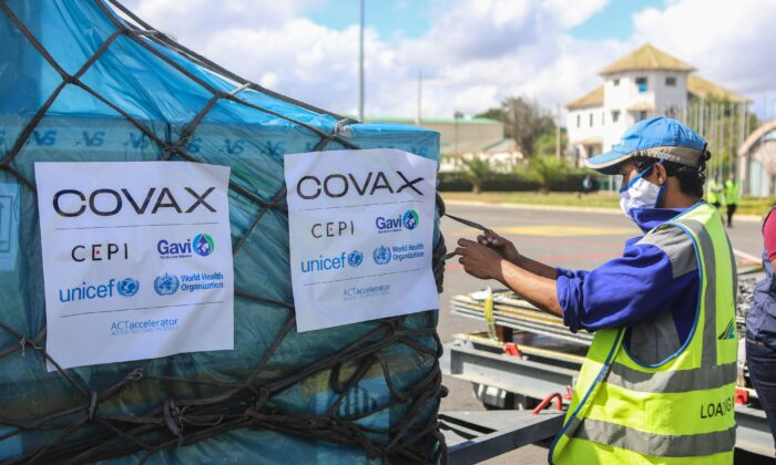 A worker handles boxes of Oxford/AstraZeneca COVID-19 vaccines, part of the the Covax programme, which aims to ensure equitable access to COVID-19 vaccinations, after they were flown into the Ivato International Airport in Antananarivo, Madagascar on May 8, 2021. (Mamyrael/AFP via Getty Images)