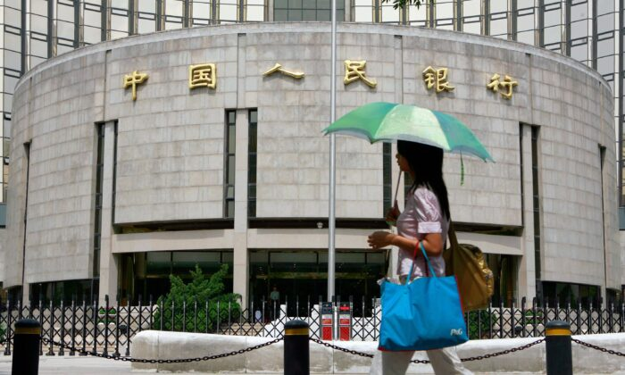 A pedestrian walks past the People's Bank of China, China's Central Bank, in Beijing in a file photo. (Teh Eng Koon/AFP via Getty Images)