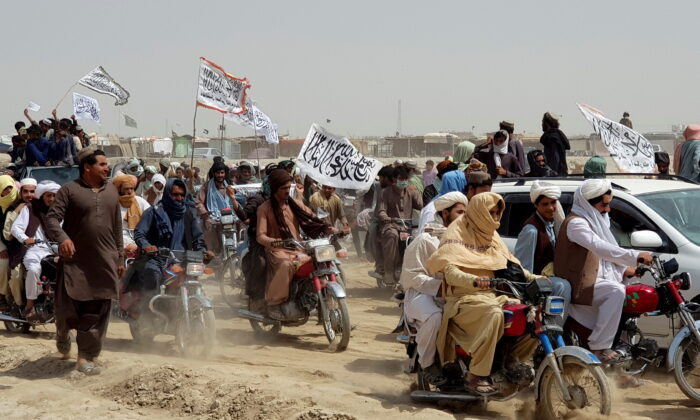 People on vehicles, holding Taliban flags, gather near the Friendship Gate crossing point in the Pakistan-Afghanistan border town of Chaman, Pakistan on July 14, 2021. (Reuters)