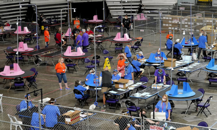 Maricopa County ballots cast in the 2020 general election are examined and recounted by contractors working for Florida-based company, Cyber Ninjas at Veterans Memorial Coliseum in Phoenix, Arizona, on May 6, 2021. (AP Photo/Matt York, Pool)