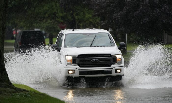 A truck drives through a flooded street, in Dearborn Heights, Mich., on July 16, 2021. (Carlos Osorio/AP Photo)