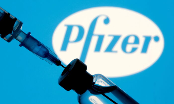 A vial and syringe are seen in front of a displayed Pfizer logo in this illustration taken Jan. 11, 2021. (Dado Ruvic/Illustration/File Photo/Reuters)