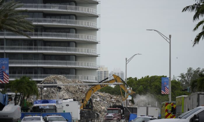 An excavator removes the rubble of the demolished section of the Champlain Towers South building, as recovery work continues at the site of the partially collapsed condo building, in Surfside, Fla., on July 12, 2021. (Rebecca Blackwell/AP Photo)