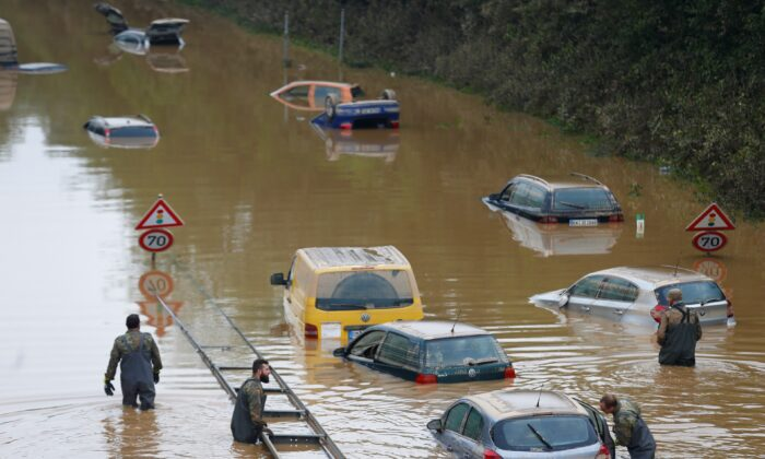 Members of the Bundeswehr forces, surrounded by partially submerged cars, wade through the flood water following heavy rainfalls in Erftstadt-Blessem, Germany, on July 17, 2021. (Thilo Schmuelgen /Reuters)