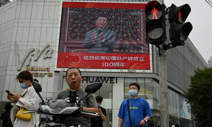 People walk in front of a large screen showing Chinese leader Xi Jinping giving a speech during celebrations to mark the 100th anniversary of the founding of the Chinese Communist Party in Beijing, China on July 1, 2021. (Noel Celis/AFP via Getty Images)