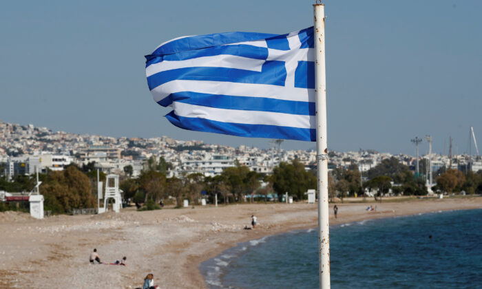 A Greek national flag flutters as people visit a beach, following a COVID-19 outbreak, in Athens, Greece, on April 28, 2020. (Goran Tomasevic/Reuters)