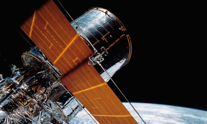 The giant Hubble Space Telescope can be seen as it is suspended in space by Discovery's Remote Manipulator System (RMS) following the deployment of part of its solar panels and antennae on April 25, 1990. (NASA via AP)
