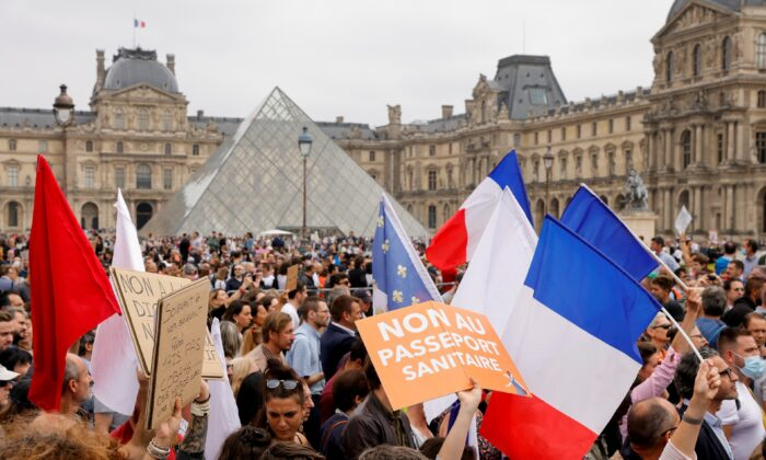 Demonstrators walk past Pyramide du Louvre during a protest against the new measures announced by French President Emmanuel Macron to fight the coronavirus disease (COVID-19) outbreak, in Paris, on July 17, 2021. (Pascal Rossignol /Reuters)