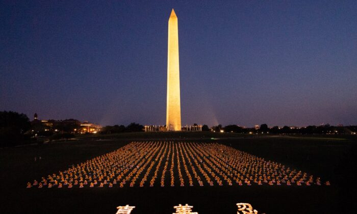 """Falun Gong practitioners at candlelight vigil remembering victims of the 22 years persecution in China at the Washington Monument on July 16, 2021. The characters for """"Truthfulness, Compassion, Tolerance,"""" the principles taught by the spiritual practice appear at the front. (Edward Dai/The Epoch Times)"""
