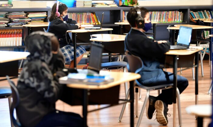 Students sit with their laptop computers in a classroom in La Puente, Calif., on Nov. 16, 2020. (Frederic J. Brown/AFP via Getty Images)