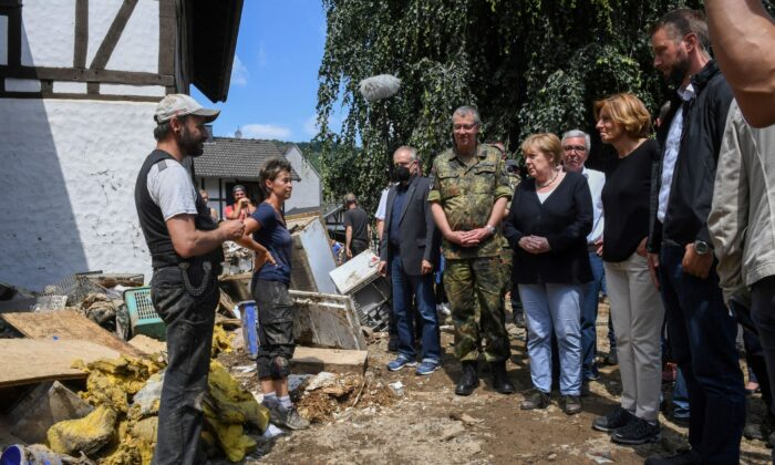 German Chancellor Angela Merkel and Rhineland-Palatinate State Premier Malu Dreyer talk to residents standing amid debris during their visit in the flood-ravaged village of Schuld near Bad Neuenahr-Ahrweiler, Rhineland-Palatinate state, on Germany, on July 18, 2021. (Christof Stache/Pool via Reuters)